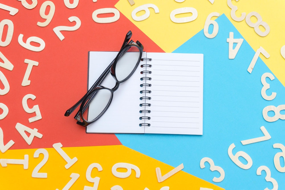 black glasses on a notebook with numbers all around